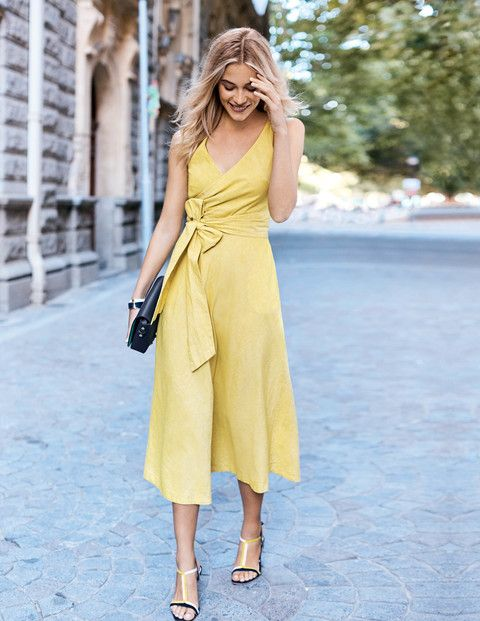wrap dress con sandalias y cartera de mano